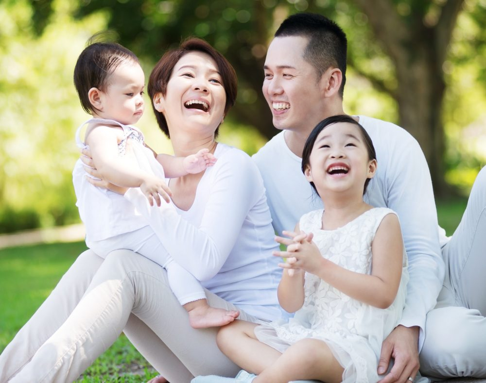 Young happy Asian family enjoying a sunny day in the park.